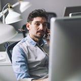 Hombre de negocios hermoso que trabaja en oficina usando el teléfono móvil Imagen de archivo libre de regalías