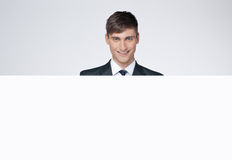 Hombre de negocios hermoso sonriente detrás del cartel blanco. Imagenes de archivo