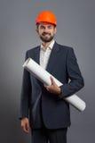 Hombre de negocios hermoso sonriente en casco anaranjado con el modelo Fotografía de archivo libre de regalías