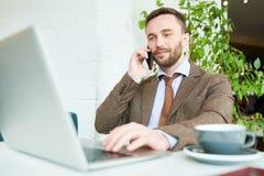 Hombre de negocios hermoso Speaking por el teléfono imagen de archivo libre de regalías