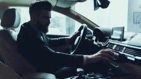 Hombre de negocios hermoso Turning Audio Button en coche imagen de archivo libre de regalías