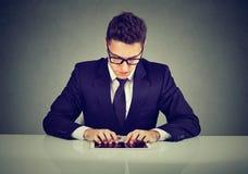 Hombre de negocios hermoso usando una tableta mientras que trabaja en el escritorio foto de archivo