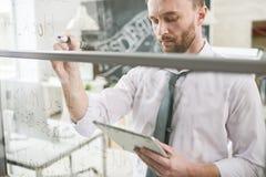 Hombre de negocios hermoso Writing en la pared de cristal foto de archivo