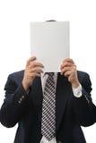 Hombre de negocios Hiding Behind Paper Imagen de archivo libre de regalías