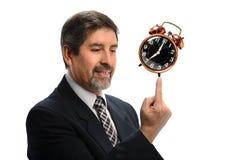 Hombre de negocios hispánico Balancing Vintage Clock imágenes de archivo libres de regalías