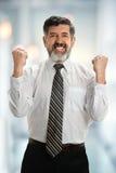 Hombre de negocios hispánico Celebrating en oficina Fotografía de archivo