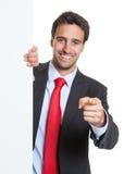 Hombre de negocios hispánico con el traje y el tablero blanco que señalan en la cámara Imagen de archivo libre de regalías