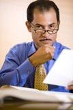 Hombre de negocios hispánico de mediana edad que trabaja en oficina Fotografía de archivo libre de regalías