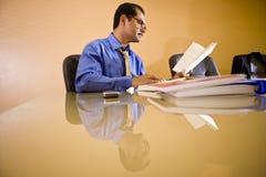 Hombre de negocios hispánico de mediana edad que trabaja en oficina Foto de archivo