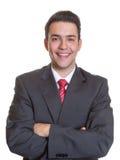 Hombre de negocios hispánico de risa con los brazos cruzados Imagen de archivo libre de regalías