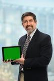 Hombre de negocios hispánico Displaying Electronic Tablet Fotografía de archivo libre de regalías