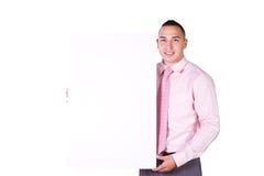 Hombre de negocios hispánico hermoso que lleva a cabo una muestra en blanco Fotografía de archivo libre de regalías