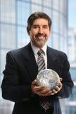 Hombre de negocios hispánico Holding Earth Foto de archivo libre de regalías