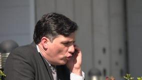 Hombre de negocios hispánico infeliz usando el teléfono almacen de metraje de vídeo