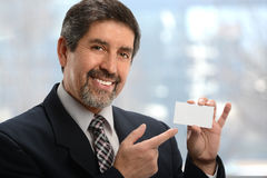 Hombre de negocios hispánico Pointing a la tarjeta de visita imágenes de archivo libres de regalías