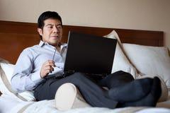 Hombre de negocios hispánico usando la computadora portátil Foto de archivo