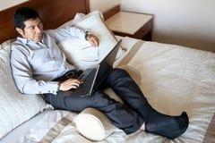 Hombre de negocios hispánico usando una computadora portátil Imagen de archivo libre de regalías