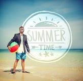 Hombre de negocios Holding Beach Ball que se coloca en la playa Foto de archivo