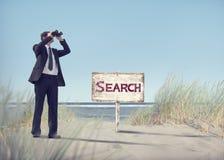 Hombre de negocios Holding Binoculars con el letrero en la playa Foto de archivo