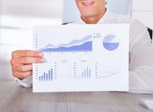 Hombre de negocios Holding Graph Printed en el papel Imagen de archivo libre de regalías