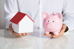 Hombre de negocios Holding House Model y Piggybank Imagen de archivo