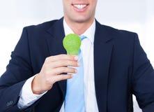 Hombre de negocios Holding Light Bulb con la hierba verde Foto de archivo