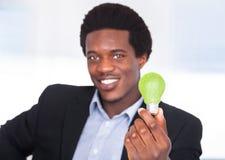 Hombre de negocios Holding Light Bulb con la hierba verde Imagen de archivo libre de regalías