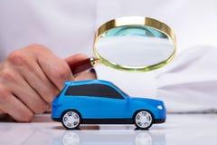 Hombre de negocios Holding Magnifying Glass sobre el coche imagen de archivo