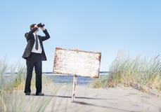 Hombre de negocios Holding Megatelescope con el letrero vacío en la playa Imágenes de archivo libres de regalías