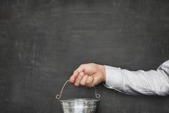 Hombre de negocios Holding Metallic Bucket contra la pizarra en blanco Imagen de archivo libre de regalías