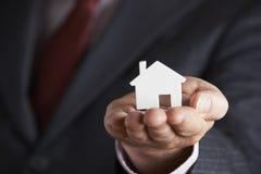 Hombre de negocios Holding Model House en la palma de la mano Imagenes de archivo