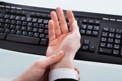 Hombre de negocios Holding Painful Wrist en el escritorio de oficina Fotos de archivo libres de regalías