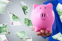 Hombre de negocios Holding Piggy Bank y el volar euro de los billetes de banco Foto de archivo libre de regalías