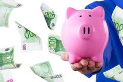 Hombre de negocios Holding Piggy Bank y el volar euro de los billetes de banco Fotografía de archivo libre de regalías