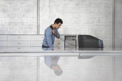 Hombre de negocios Holding Telephone Receiver mientras que usa el ordenador Imagen de archivo