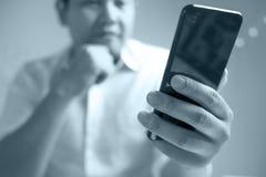 Hombre de negocios Holding y usar el teléfono elegante imagen de archivo libre de regalías