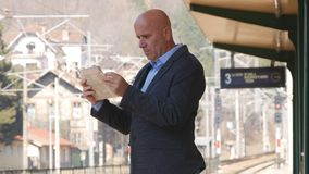 Hombre de negocios Image Reading Newspaper en una estación de tren imagen de archivo libre de regalías