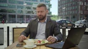 Hombre de negocios impaciente que come el almuerzo que espera alguien en el café, steadicam metrajes