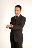Hombre de negocios impaciente que señala en el reloj Fotos de archivo