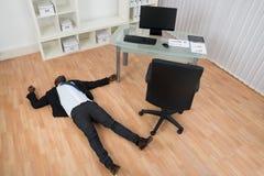 Hombre de negocios inconsciente Lying On Floor Foto de archivo