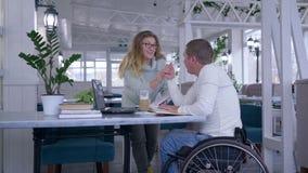 Hombre de negocios independiente discapacitado, creativo acertado en silla de ruedas con la mujer discutir negocio de lanzamiento almacen de video