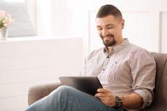 Hombre de negocios independiente encantado usando una tableta Imagen de archivo libre de regalías