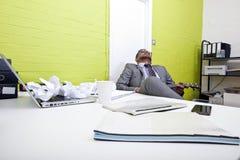 Hombre de negocios indio dormido en su escritorio que agarra el ukelele fotografía de archivo