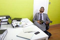 Hombre de negocios indio dormido en su escritorio que agarra el ukelele imágenes de archivo libres de regalías