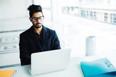 Hombre de negocios indio que trabaja en el ordenador portátil en oficina moderna fotografía de archivo
