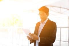 Hombre de negocios indio usando la PC de la tableta en el ferrocarril Imágenes de archivo libres de regalías