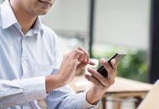 Hombre de negocios indio usando smartphone mientras que almorzando Imagenes de archivo