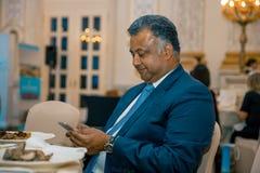 Hombre de negocios indio usando su smartphone en una recepción oficial en un restaurante Fotos de archivo