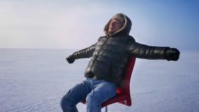 Hombre de negocios infantil alegre en capa y capilla calientes en el desierto de la nieve que hace girar alrededor en silla roja almacen de metraje de vídeo