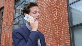 Hombre de negocios infeliz Walking y el hablar en el teléfono, tenso y frustrado almacen de video